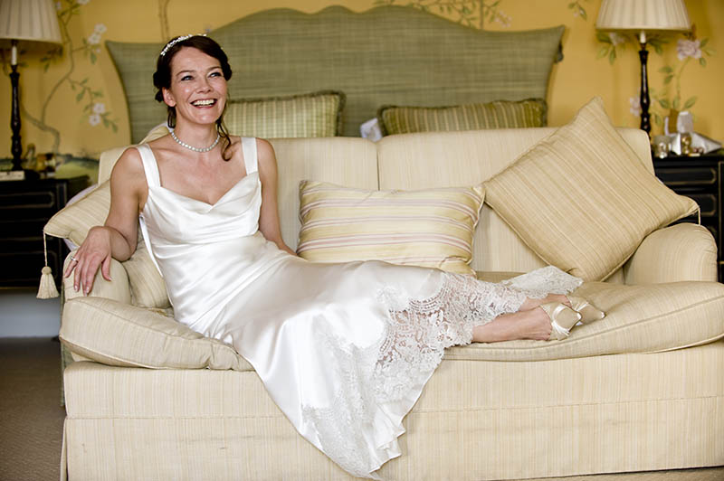 bride laughs in her wedding dress in the chinese room at chandos house
