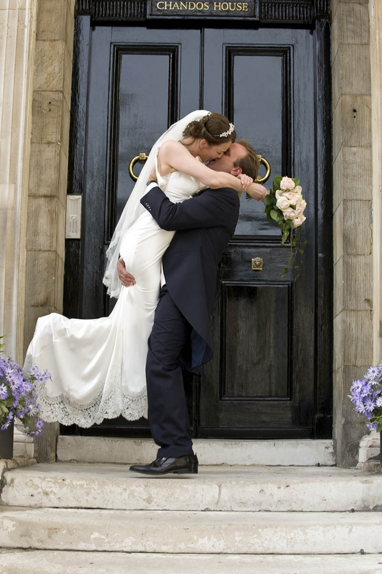 bride and groom on the steps of chandos house after their wedding