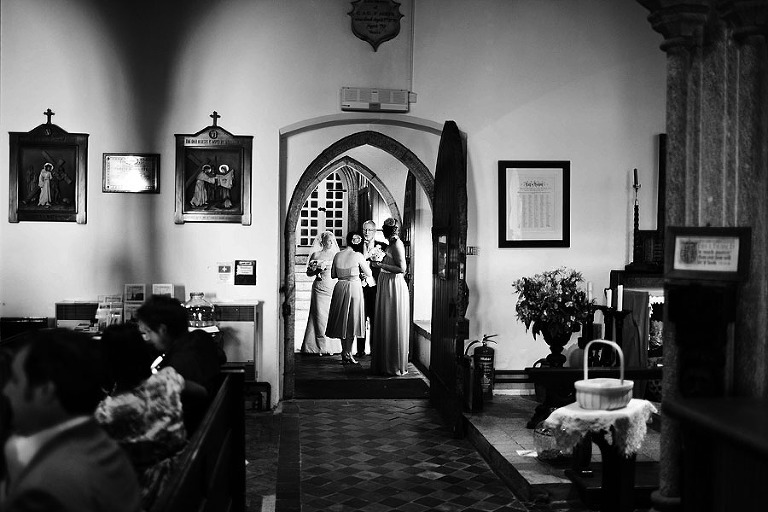 BRIDE AND FATHER STAND IN DOORWAY OF CHURCH AT WEDDING IN LONDON