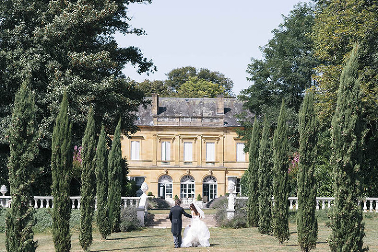 at chateau la durantie bride and groom walk along avenue of cypress trees