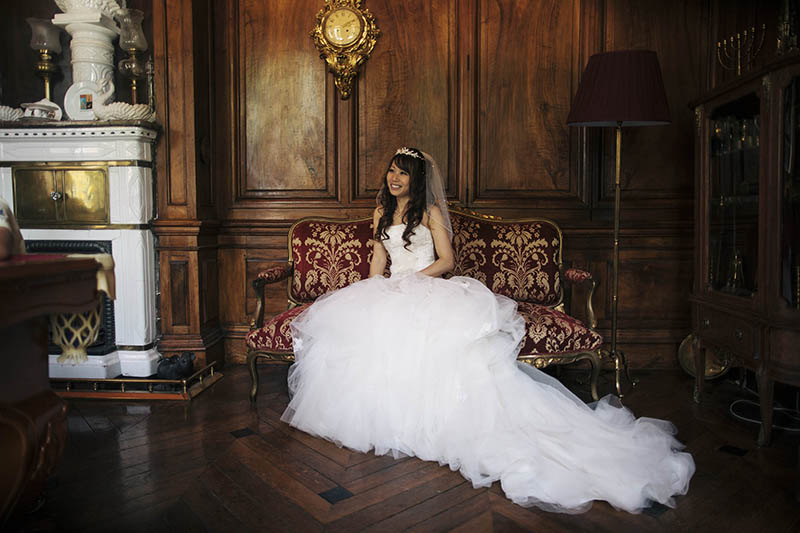 bride in wedding dress sat in pool room of chateau la durantie