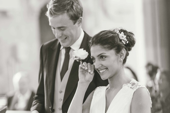 bride wipes a tear from her eye during her wedding in wiltshire