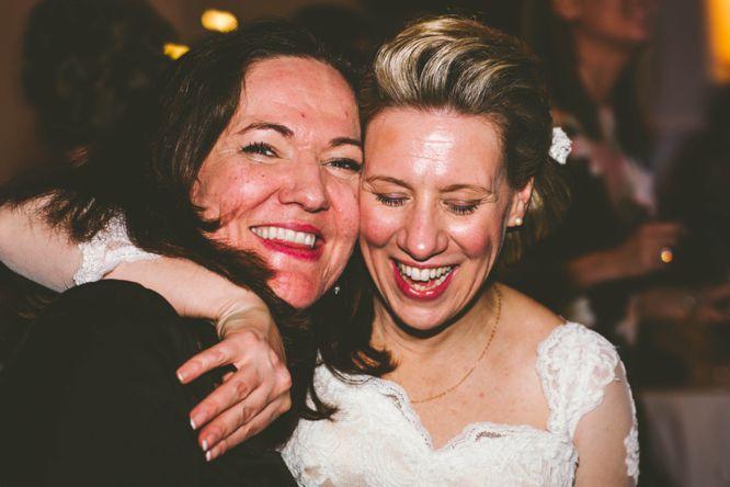 bride hugs friend on dance floor