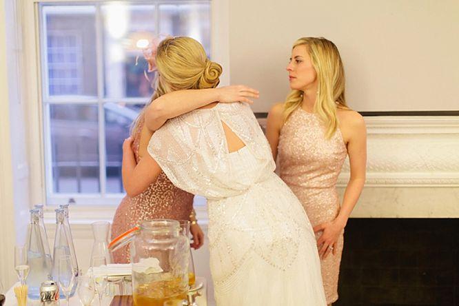 bride hugs sister at wedding wearing jenny packham