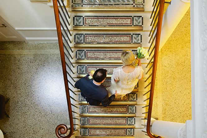 bride and groom on stairs of royal society arts london