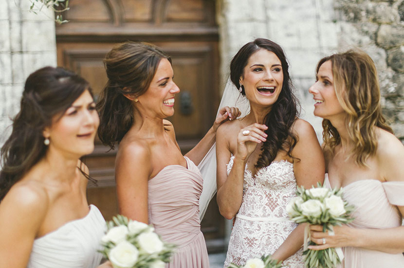 bride and her bridesmaids laugh outside french chateau