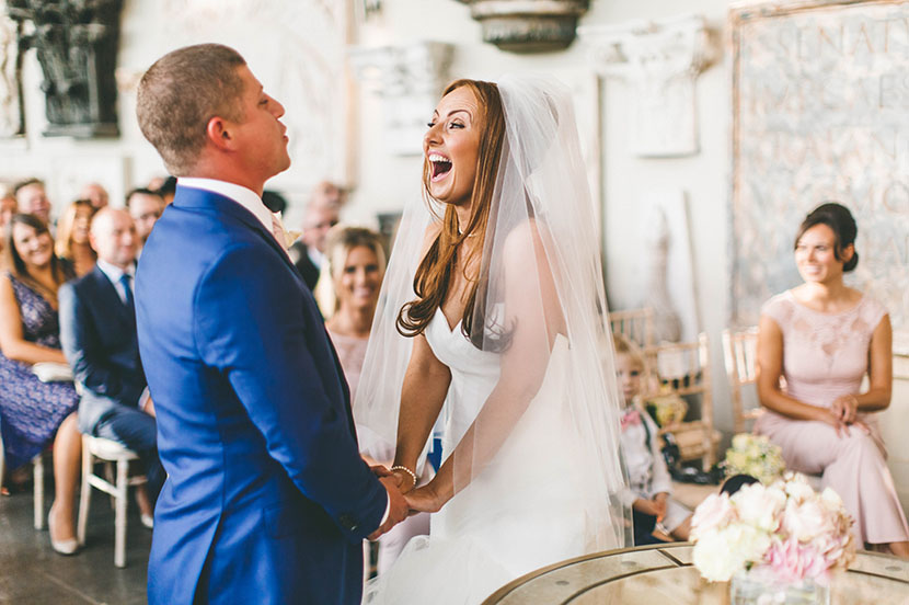 bride and groom laugh whilst reading vows